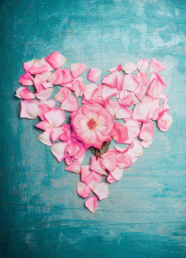 Cuore fatto dei petali rosa rosa sul fondo blu del turchese, vista superiore Giorno romantico e di biglietti di S. Valentino di a immagine stock