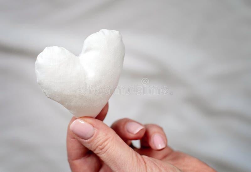 Cuore fatto a mano bianco del tessuto in mano della donna nell'immagine di sfondo grigia fotografie stock libere da diritti