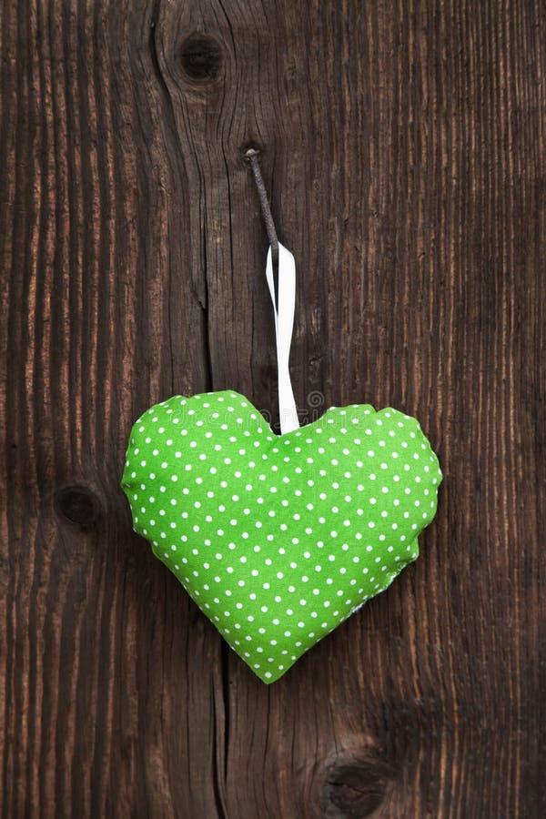 Cuore fatto a mano verde mela del tessuto con i pois che appendono sull' fotografia stock libera da diritti