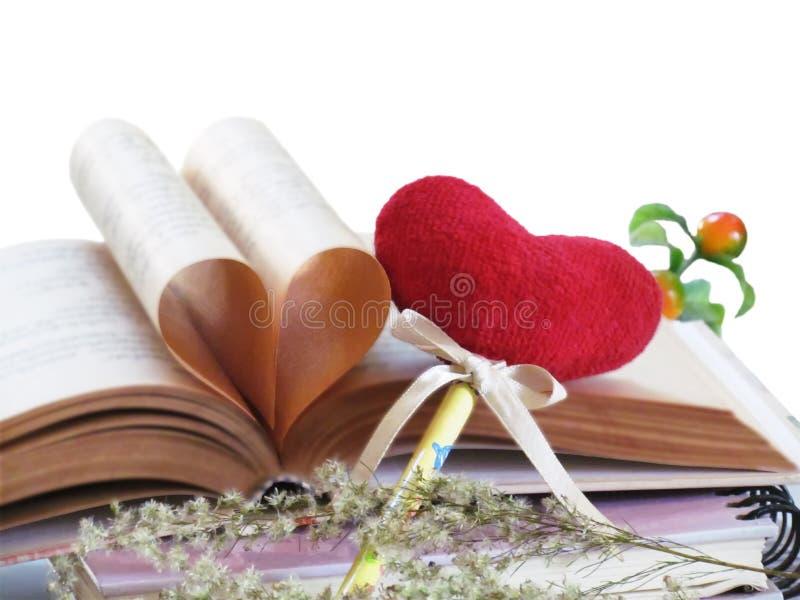 Cuore a forma di fatto delle pagine del vecchio libro e del cuore rosso del segnalibro isolati su backgrond bianco Fuoco selettiv immagini stock