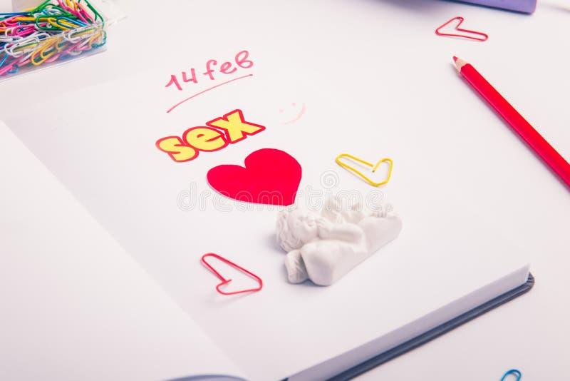Cuore, iscrizione di parola del sesso e stauette rossi di angeli sull'organizzatore personale sul posto di lavoro Concetto di pia fotografia stock