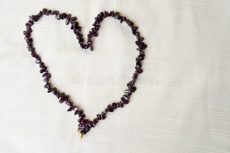 Cuore per il giorno del ` s del biglietto di S. Valentino fatto di belle perle femminili, collane delle pietre scure marroni, amb fotografia stock
