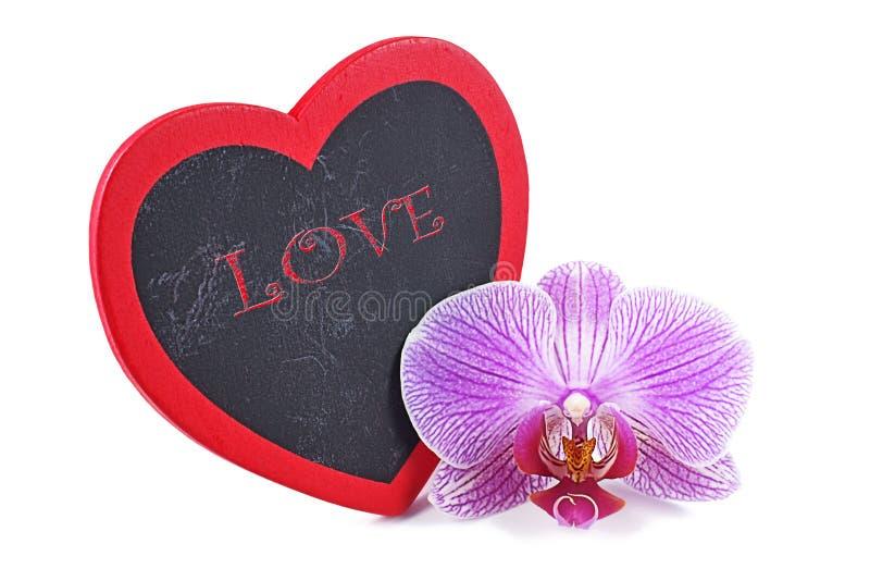 Cuore, placca di legno nel cuore di forma ed orchidee, giorno del ` s del biglietto di S. Valentino fotografia stock libera da diritti