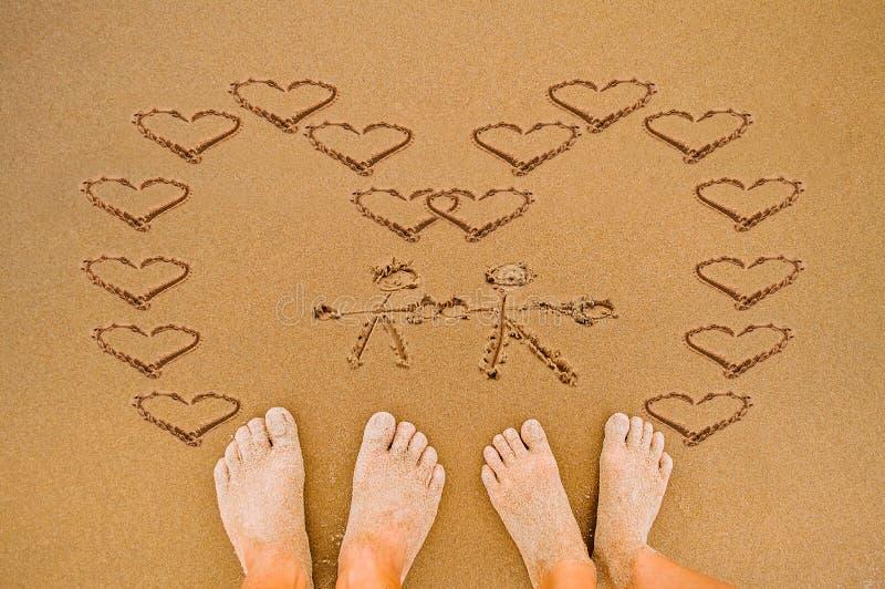 Cuore romantico di amore di tiraggio sulla spiaggia immagine stock