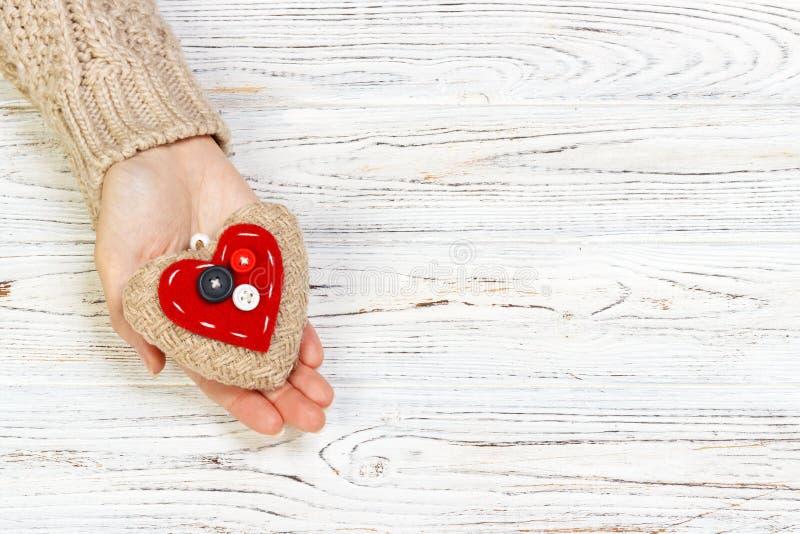 Cuore rosso astratto che tricotta nella mano per il giorno del ` s del biglietto di S. Valentino tono di immagine d'annata su bac fotografia stock libera da diritti