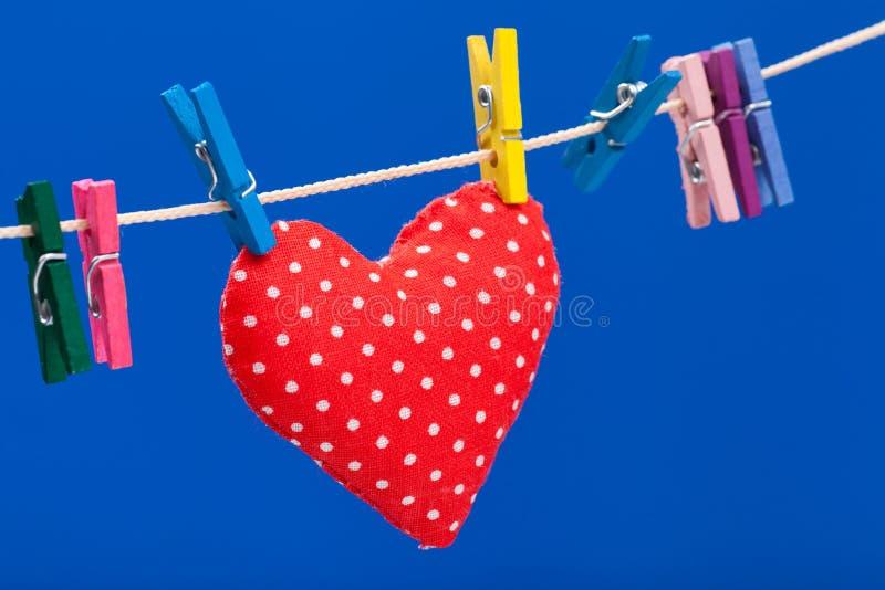 Cuore rosso che appende su un clothesline con i clothespins immagine stock libera da diritti