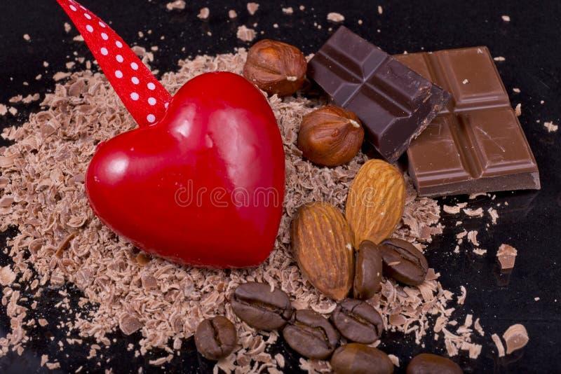 Cuore rosso con i chicchi di caffè, il cioccolato, le mandorle e le nocciole immagini stock libere da diritti