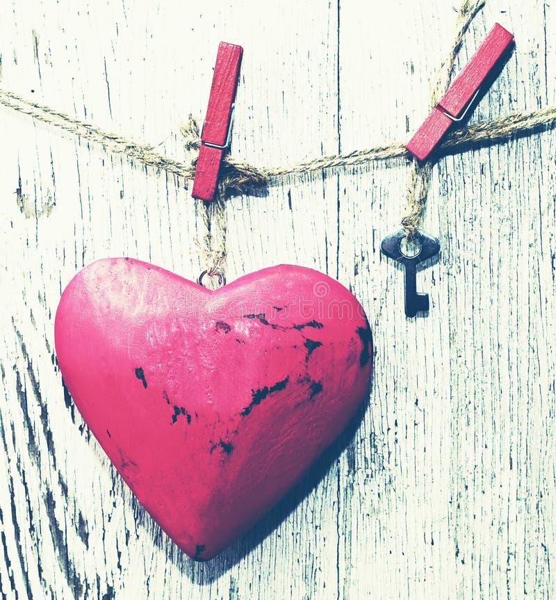 Cuore rosso decorativo e piccola chiave del metallo su una corda contro lo sfondo di un bordo bianco anziano fotografia stock libera da diritti