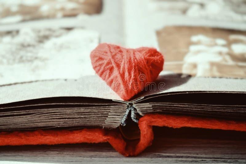Cuore rosso del filo sull'album di foto aperto sul fondo di legno della tavola Libro d'annata o album di foto con il cuore del fi fotografia stock