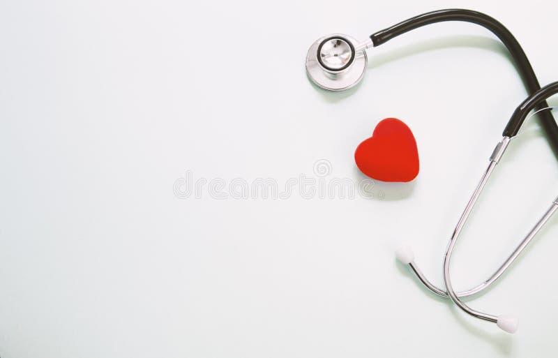 Cuore rosso e uno stetoscopio sullo scrittorio immagine stock