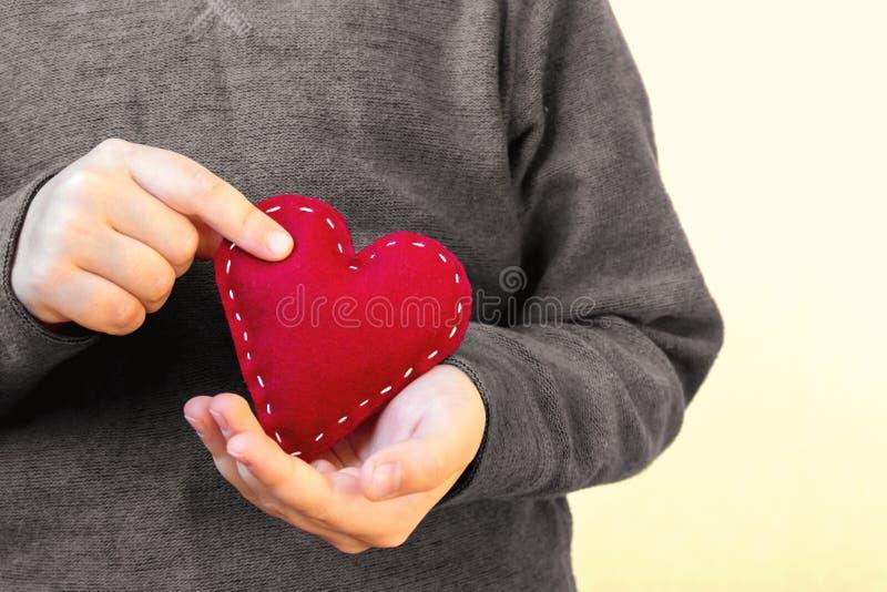 Cuore rosso in mani del bambino fotografie stock