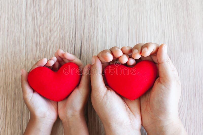 Cuore rosso in mani del bambino e mani del genitore sul fondo di legno della tavola immagine stock