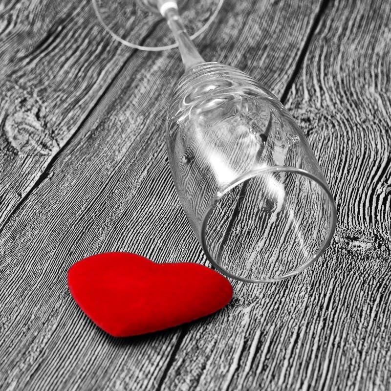 Cuore rosso sotto vetro vuoto di alcool su fondo in bianco e nero Il concetto di distruzione della famiglia dovuto alcool fotografie stock libere da diritti