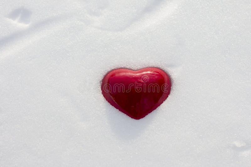 Cuore rosso su neve bianca fotografia stock