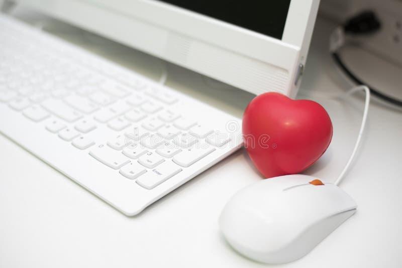 Cuore rosso in ufficio con l'insieme dello scrittorio del computer Mini e piccola dimensione del cuore della spugna per l'antispa fotografia stock
