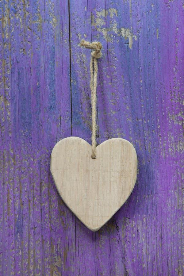 Cuore rustico su superficie di legno porpora per il biglietto di S. Valentino, compleanno, m. fotografia stock