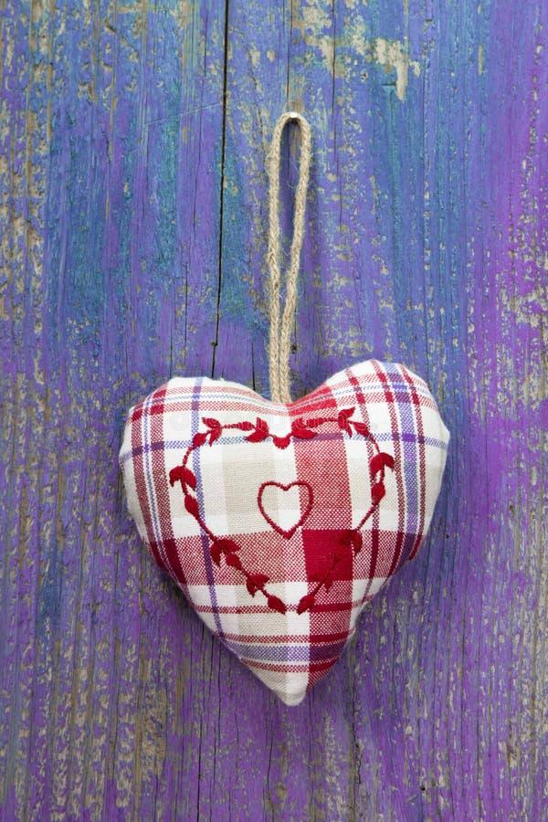 Cuore rustico su superficie di legno porpora per nozze, compleanno, val fotografie stock libere da diritti