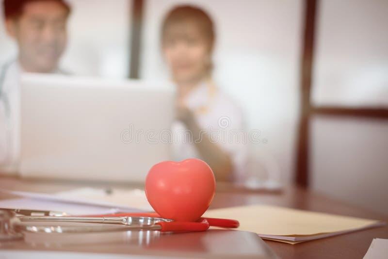 Cuore & stetoscopio rossi sullo scrittorio con medico che discute paziente t fotografia stock