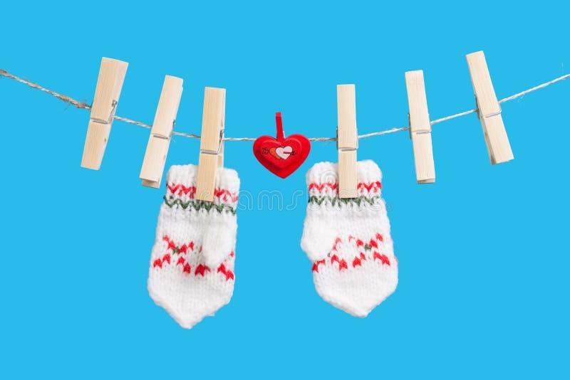 Cuore sul clothesline con i clothespins, due guanti fotografia stock libera da diritti