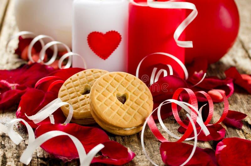 Cuori dei biscotti in petali rosa e nelle candele Fuoco selettivo fotografia stock libera da diritti