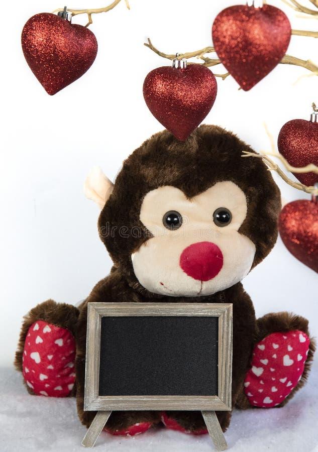 Cuori della carta del biglietto di S. Valentino e mancanza forante della scimmia alesata immagini stock