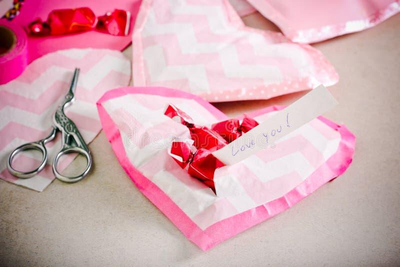 Cuori di carta fatti a mano pieni di caramelle immagini stock