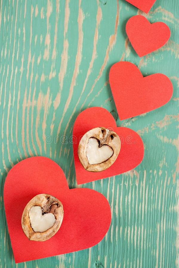 Cuori di carta rossi con due metà della noce come cuore su fondo di legno strutturato dipinto verde chiaro fotografia stock libera da diritti