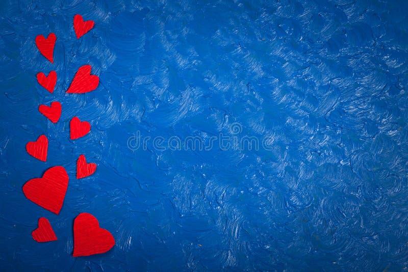 Cuori di carta rossi su un San Valentino blu del fondo immagine stock libera da diritti