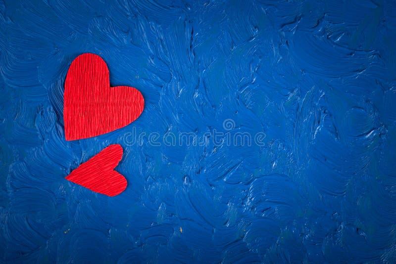 Cuori di carta rossi su un San Valentino blu del fondo fotografia stock