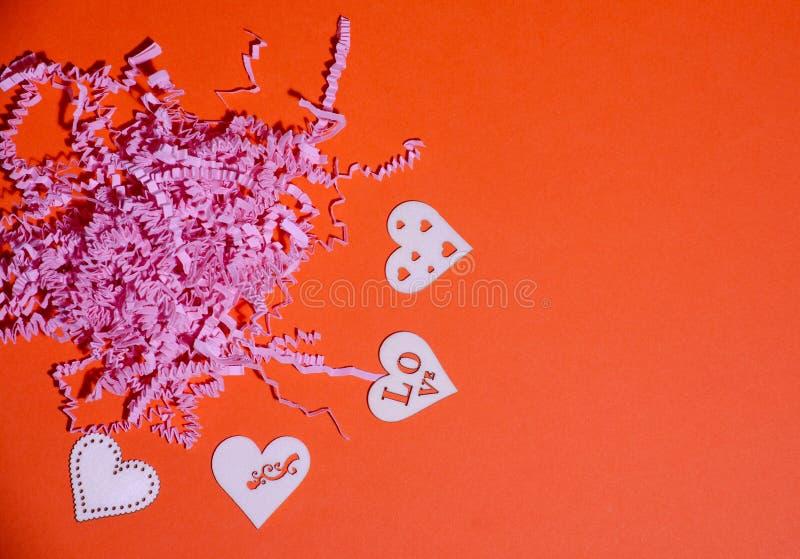 Cuori di legno sui precedenti di carta arancio con carta affettata rosa Fondo di giorno di biglietti di S. Valentino con i cuori  immagine stock