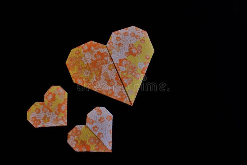 Cuori di origami su un fondo nero immagine stock