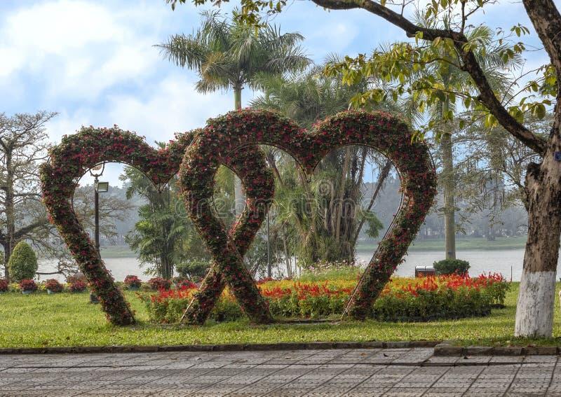 Cuori fatti dei fiori con altri fiori rossi e gialli ed il fiume di Parfume nei precedenti durante il Tet nella tonalità, Vietam immagine stock