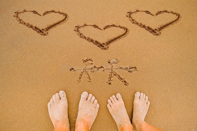 Cuori romantici di amore di tiraggio sulla spiaggia fotografia stock