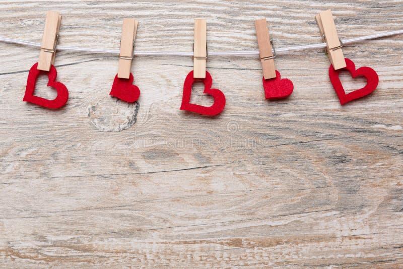 Cuori rossi con le mollette da bucato su un guinzaglio appeso immagine stock libera da diritti