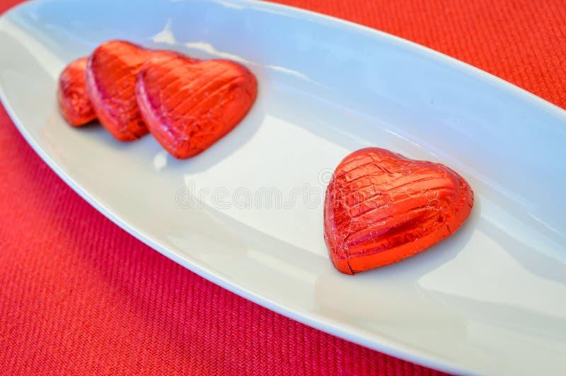 Cuori rossi del cioccolato su un piatto ceramico Giorno del `s del biglietto di S fotografie stock