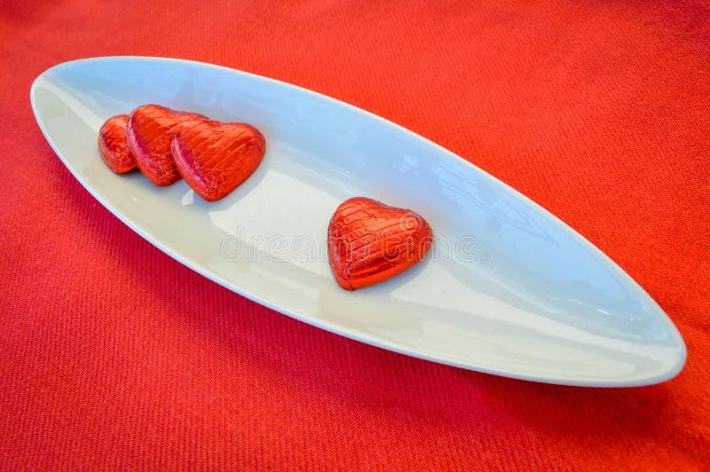 Cuori rossi del cioccolato su un piatto ceramico Giorno del `s del biglietto di S fotografia stock libera da diritti