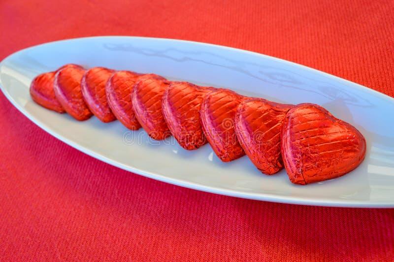 Cuori rossi del cioccolato su un piatto ceramico Giorno del `s del biglietto di S fotografia stock