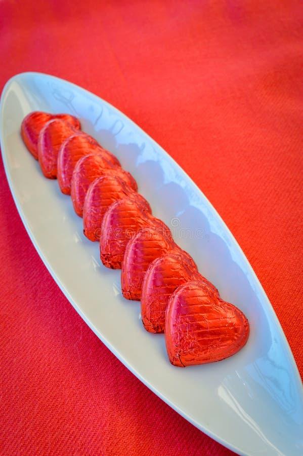 Cuori rossi del cioccolato su un piatto ceramico Giorno del `s del biglietto di S fotografie stock libere da diritti