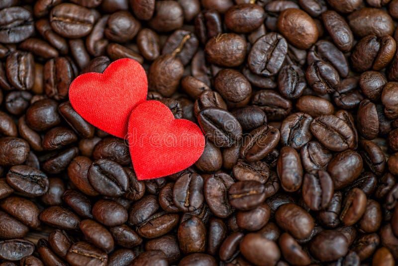 Cuori rossi del raso sul fondo di giorno dei chicchi di caffè, dei biglietti di S. Valentino o di madri, celebrazione di amore immagini stock libere da diritti