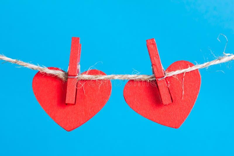 Cuori sul clothesline con i clothespins, fondo blu immagini stock libere da diritti