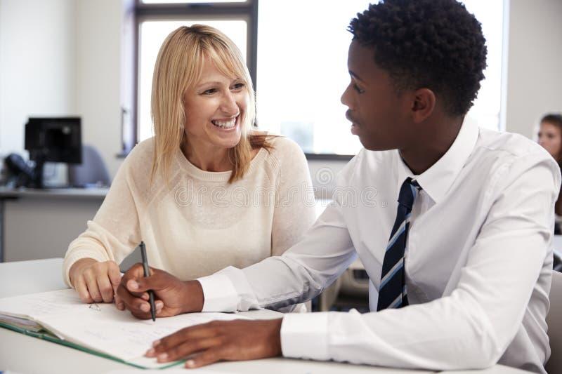 Cuota de One To One del estudiante de Giving Uniformed Male del profesor particular de la escuela secundaria en el escritorio en  foto de archivo