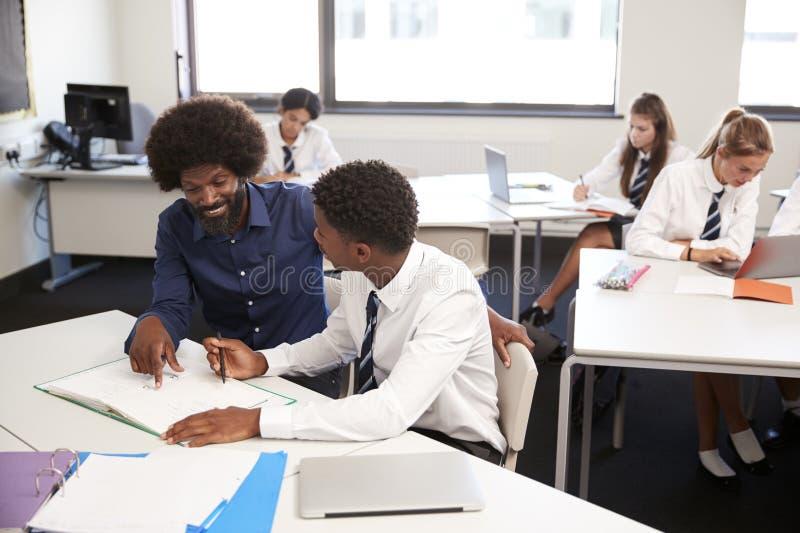 Cuota de One To One del estudiante de Giving Uniformed Male del profesor particular de la escuela secundaria en el escritorio en  imagenes de archivo