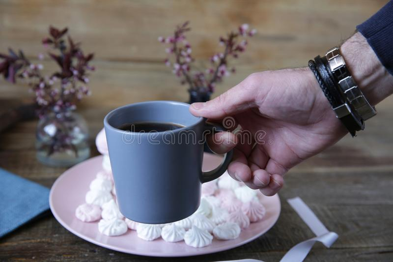 Cup of American coffee in the hand of a man on the background of marshmallow in a pink plate and spring flowers on a wooden rust stock image