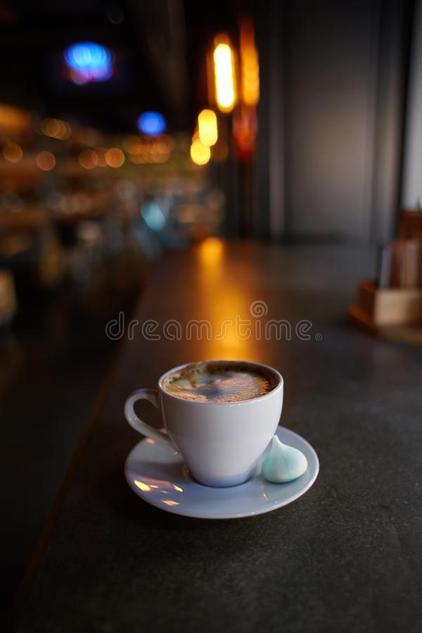 Cup of americano coffee in a white cup with a marshmallow on a saucer, royalty free stock photo