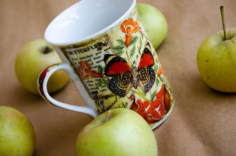 Cup. Apples Green apples. Apples and a mug. Mug with butterfly pattern. Bright mug stock image