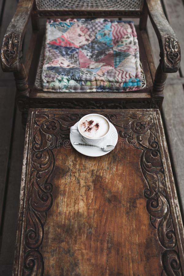 Cup of aroma cappuccino on vintage wooden table, handmade carving texture. Bali style royalty free stock photo