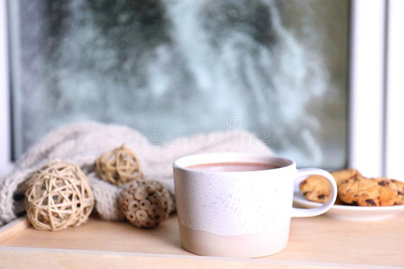 Cup of aromatic cacao on wooden tray near window. Closeup royalty free stock photo