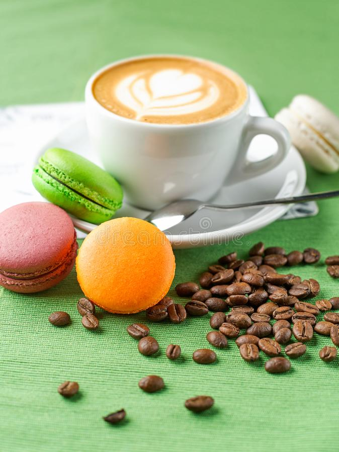 Cup of aromatic coffee cappuccino with colored cookies stock images