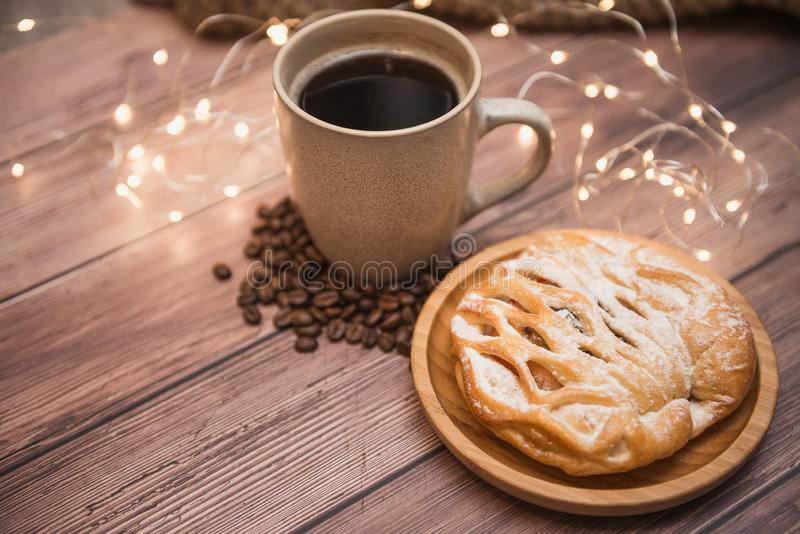 Cup of aromatic coffee, sweet pastry, coffee grains and Christmas lights on a wooden background, selective focus. Winter drinks b stock images