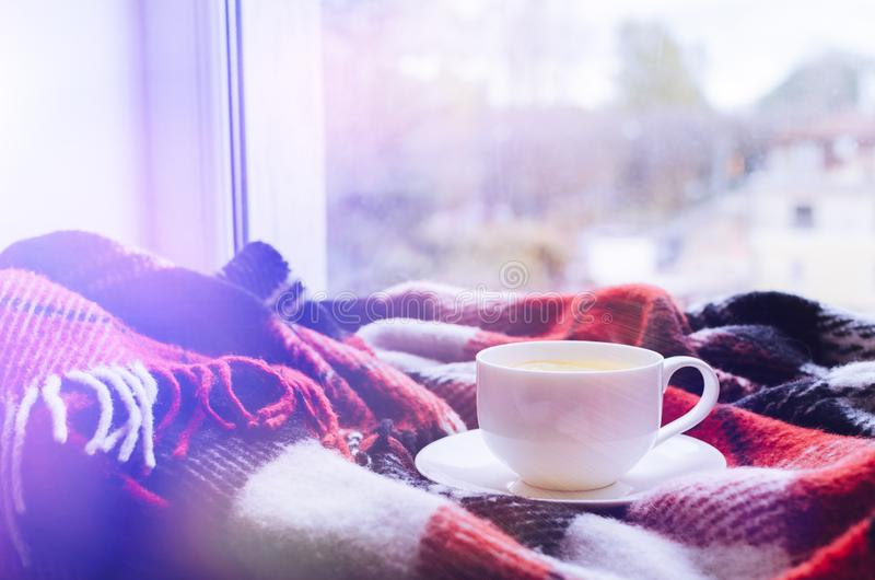 Cup of autumn tea. Cup of tea with lemon and warm woolen blanket on window sill. Hot drink for rainy days. Hygge concept, autumn mood. Cozy winter morning at royalty free stock photos